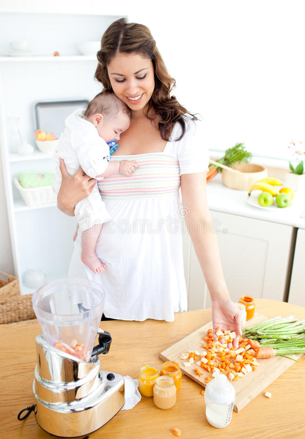 Gevende moeder die groenten voor haar baby voorbereidt royalty-vrije stock afbeeldingen