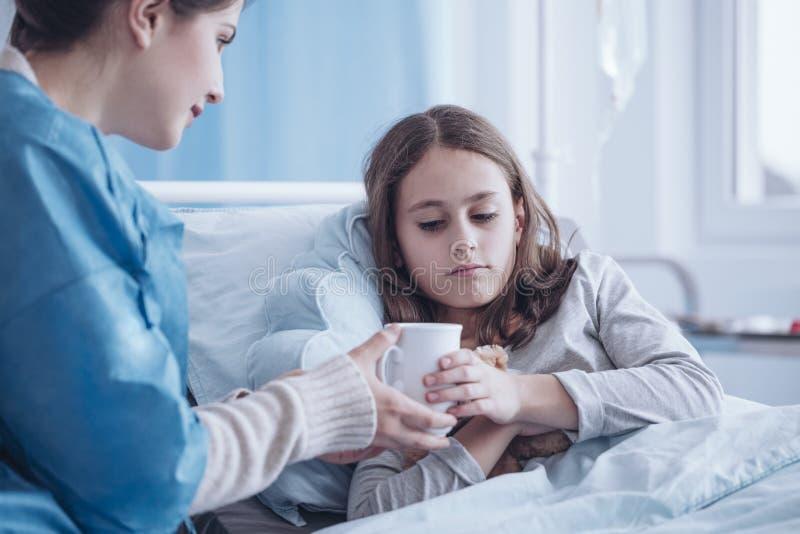 Gevende moeder die hete thee geven aan zieke dochter in de kliniek royalty-vrije stock fotografie