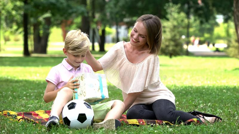 Gevende moeder die huidige doos geven aan zoon, verjaardagsviering in openlucht, verrassing stock fotografie