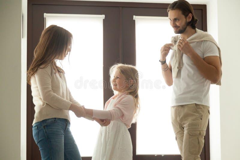 Gevende moeder die weinig dochter helpen die zich voor gang met vet kleden stock fotografie