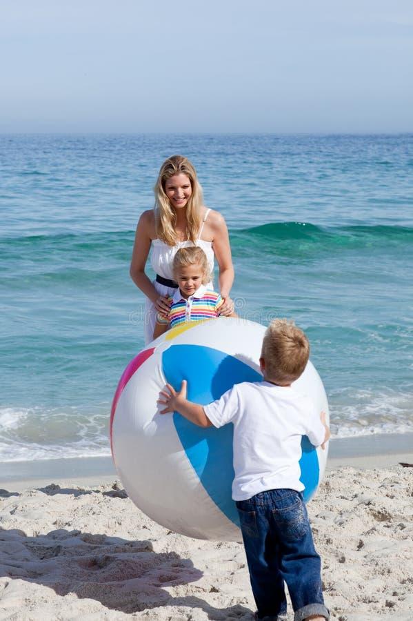 Gevende moeder en haar kinderen die met een bal spelen stock fotografie
