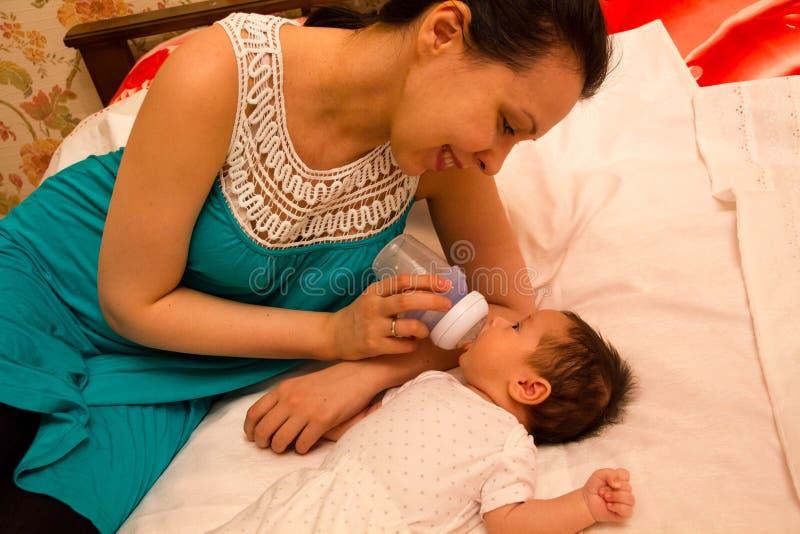 Gevende moeder van een pasgeboren baby het voeden consumptiemelk stock foto's