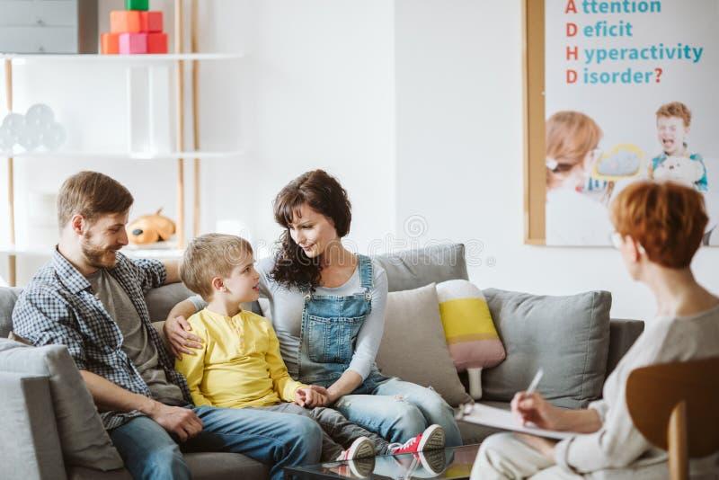 Gevende ouders en zich slecht gedragende jongen tijdens therapiezitting met adviseur royalty-vrije stock afbeelding