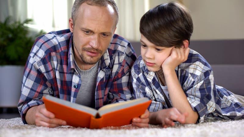 Gevende papa die zijn schooljongen helpen om moeilijk onderwerp, thuiswerk te begrijpen royalty-vrije stock afbeelding