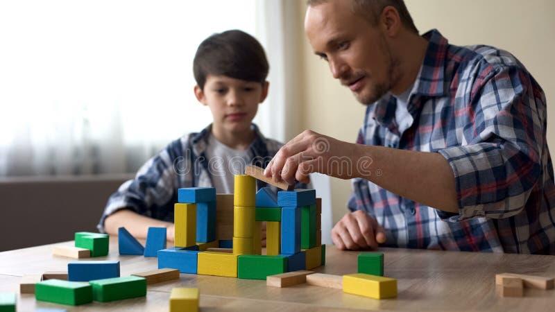 Gevende papa en zijn glimlachende zoon die gekleurde stuk speelgoed kubussen spelen thuis, kinderjaren royalty-vrije stock afbeelding
