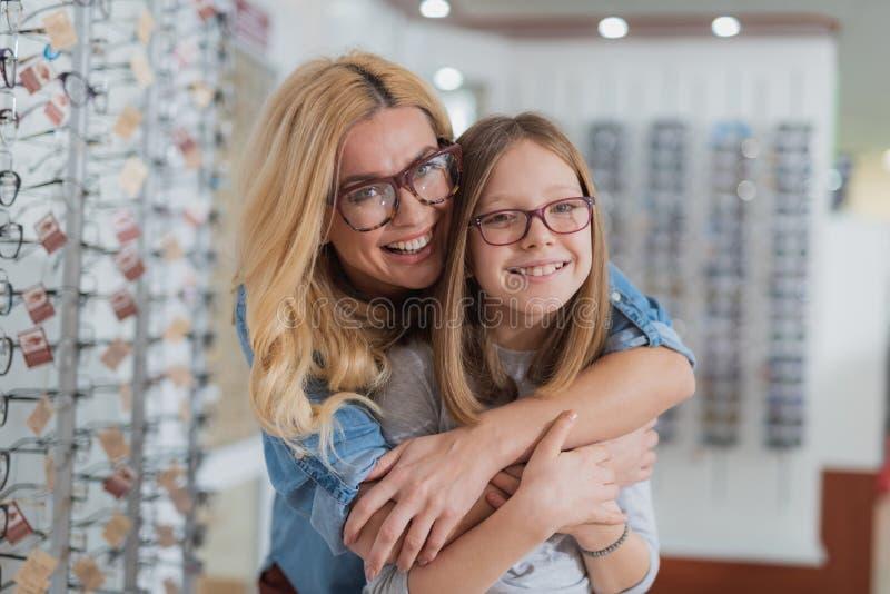 Gevende positieve moeder die haar glimlachende dochter omhelzen stock fotografie