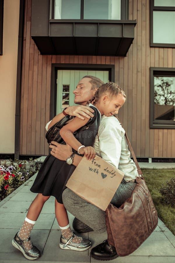Gevende positieve papa die strak jonge dochter koesteren vóór schooldag stock afbeelding