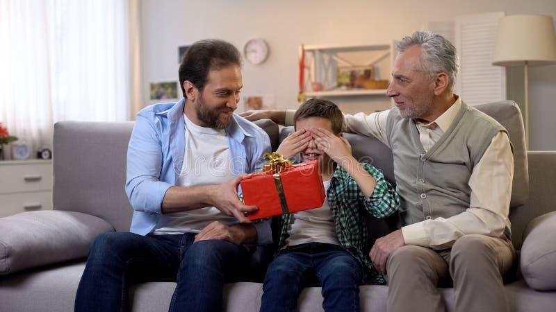 Gevende vader die giftbox aan weinig zoon met gesloten ogen geven, verjaardagsverrassing stock afbeelding