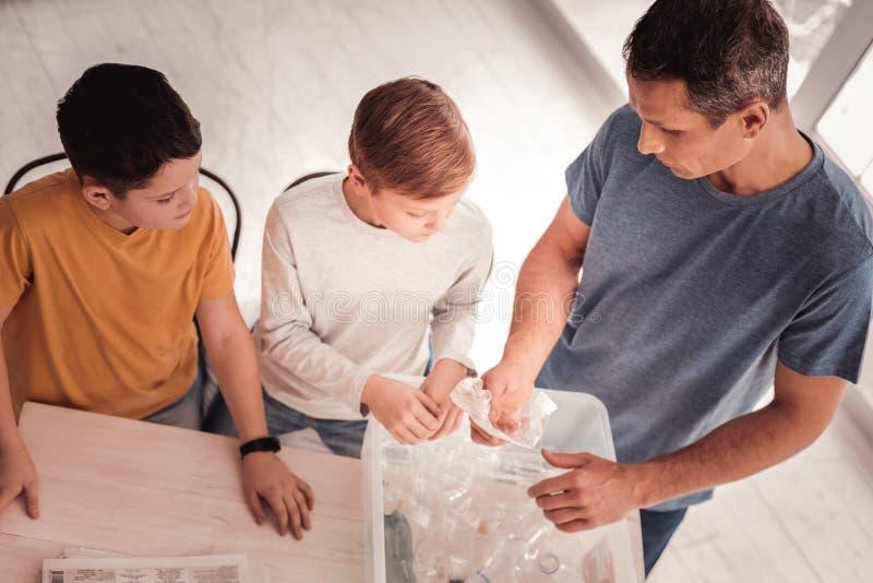 Gevende vader die met zijn kinderen over plastiek spreken royalty-vrije stock foto