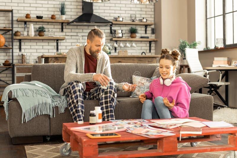 Gevende vader die zijn gedeprimeerde dochter sommige kalmeringsmiddelen geven royalty-vrije stock afbeelding