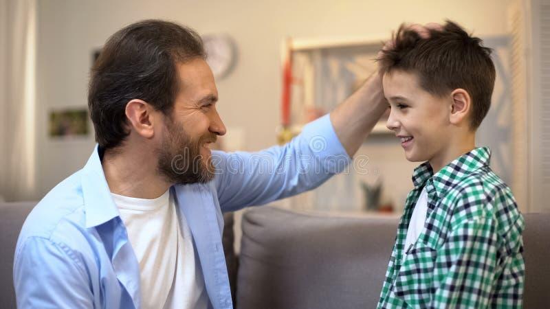 Gevende vader die zijn kleine zoon op hoofd, warme familieverhoudingen strijken, liefde royalty-vrije stock foto