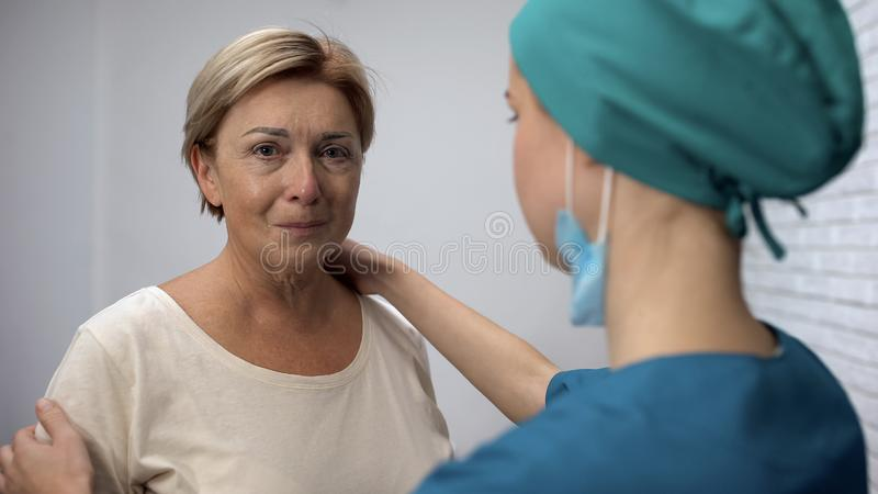 Gevende verpleegster ondersteunend volwassen vrouw met slechte diagnose, kanker in vroege stadia royalty-vrije stock afbeelding