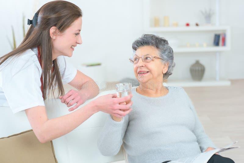 Gevende verpleegsters ondersteunende patiënt stock foto's