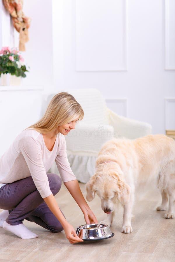Gevende vrouw die de hond voeden stock foto's