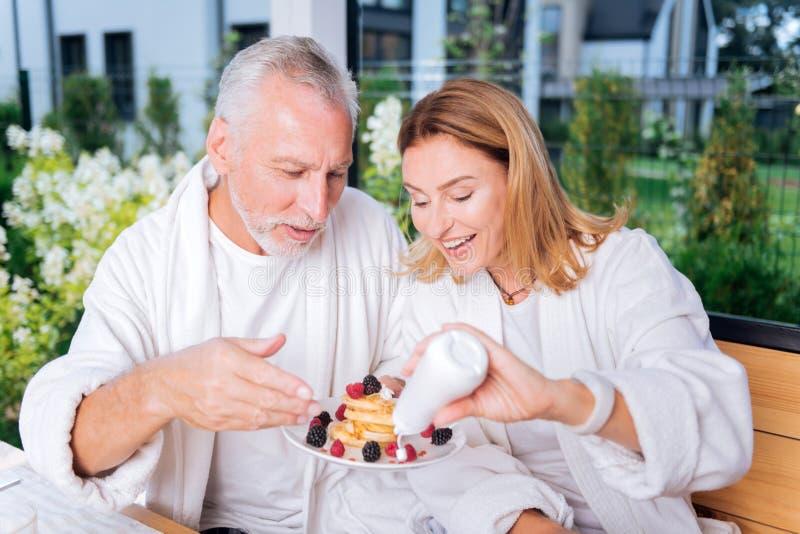 Gevende vrouw die haar gebaarde echtgenoot helpen die vanillebovenste laagje op pannekoeken zetten royalty-vrije stock afbeeldingen