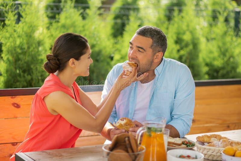 Gevende vrouw die terwijl het geven van één of ander croissant haar echtgenoot glimlachen royalty-vrije stock foto
