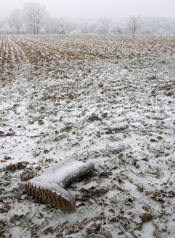 Gevergeten laarzen in het veld, bedekt met sneeuw en hoarfrost royalty-vrije stock afbeeldingen