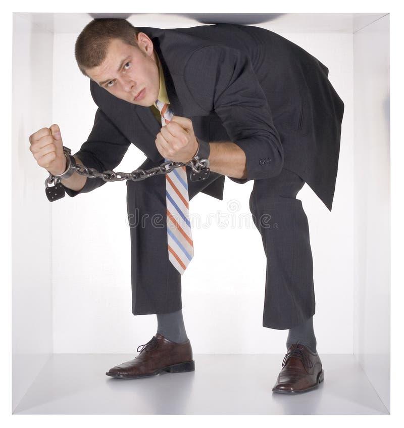 Geverketteter Geschäftsmann im Würfel stockfotos