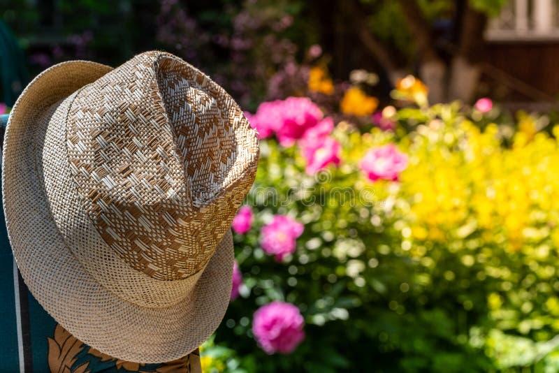 Gevlechte de zomerhoed van mensen Vage achtergrond van bloemen stock afbeelding