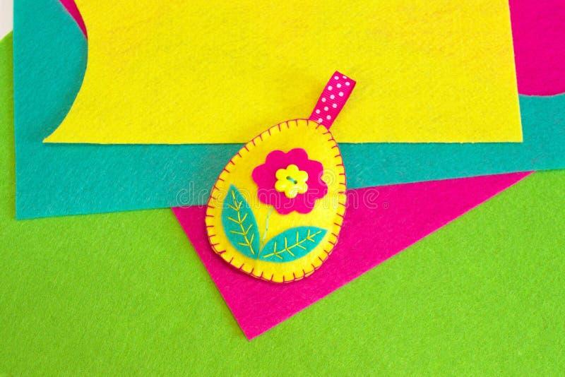 Gevoeld paaseidecor met bloem en bladeren, kleurrijke gevoelde stukken op een groene achtergrond De gemakkelijke naaiende ambacht stock foto