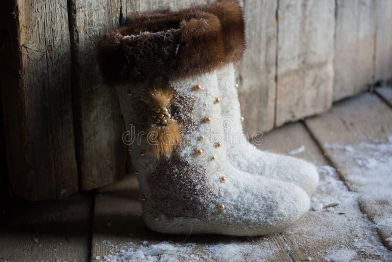Gevoelde laarzen dichtbij de houten deur stock afbeeldingen