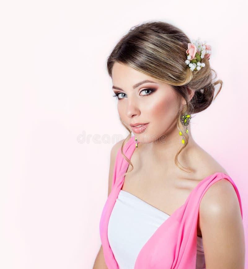 Gevoelig beeld van een mooi vrouwenmeisje zoals een bruid met helder make-upkapsel met bloemenrozen in het hoofd in een roze kled stock afbeelding