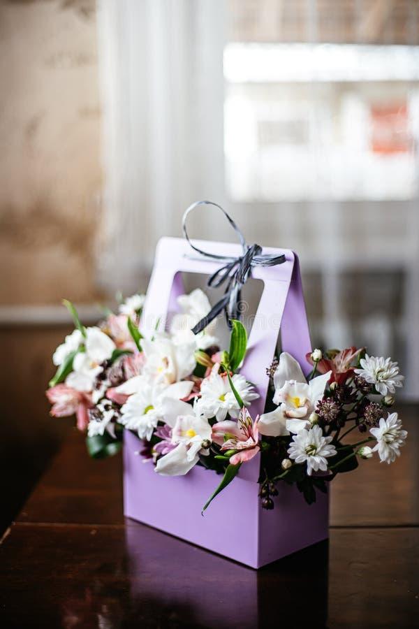 Gevoelig en mooi giftboeket van bloemen in een purpere cortonalmand Close-up Bloemen royalty-vrije stock afbeeldingen