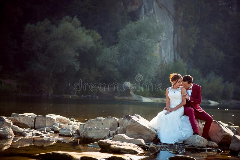 Gevoelig portret van de bruidegom die in rood kostuum de aanbiddelijke bruid in de schouder kussen terwijl dichtbij het zitten op stock foto's