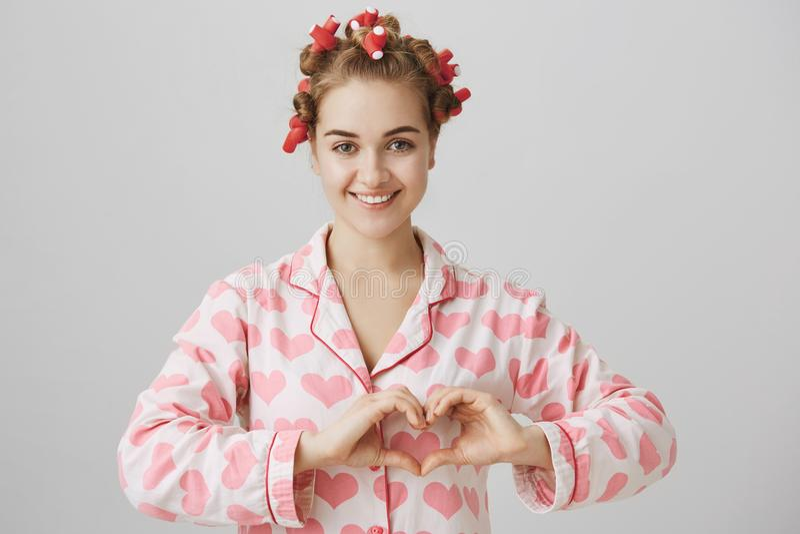 Gevoels charmante Europese vrouw in haar-krulspelden en pyjama, kijkend vrouwelijk en tonend hartgebaar over borst royalty-vrije stock foto's
