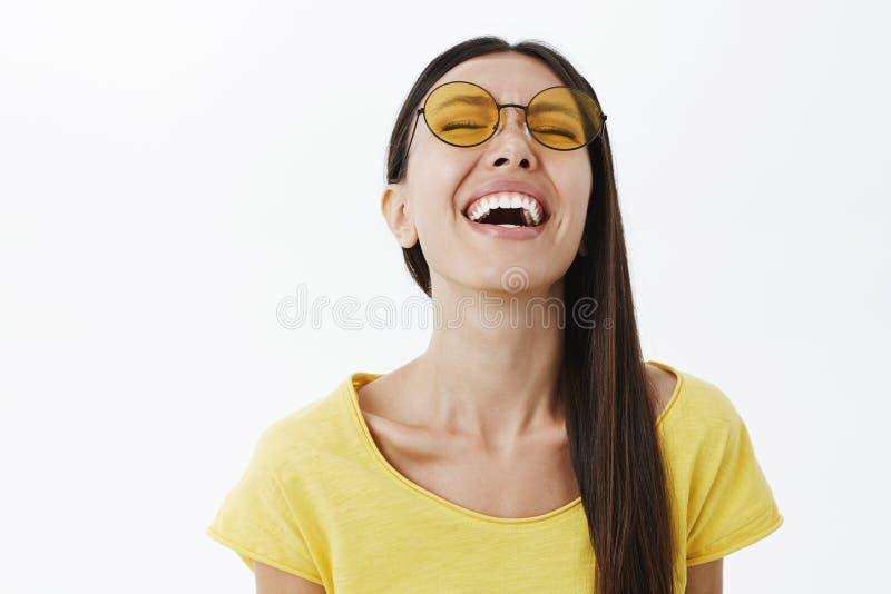 Gevoels onbezorgd en vrolijk aantrekkelijk wijfje met donker haar in rond geel zonnebril opheffend hoofd omhoog terwijl het lache royalty-vrije stock fotografie