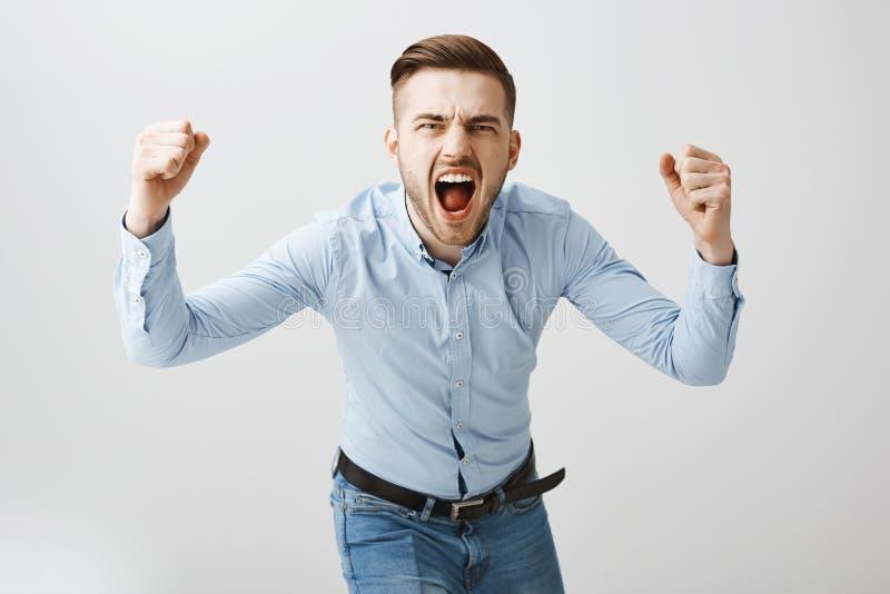 Gevoels opgewonden betrokken Europese mannelijke werkgever in formeel blauw overhemd en jeans die naar en camera buigen die schre stock foto's
