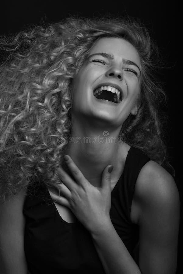 Gevoels zwart-wit studioportret van leuke jonge vrouw met krullend haar royalty-vrije stock afbeelding
