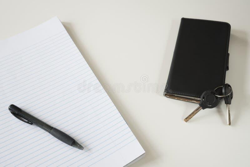Gevoerd document met zwarte pen, sleutels en smartphone, op wit bureau Ruimte voor tekst stock foto's