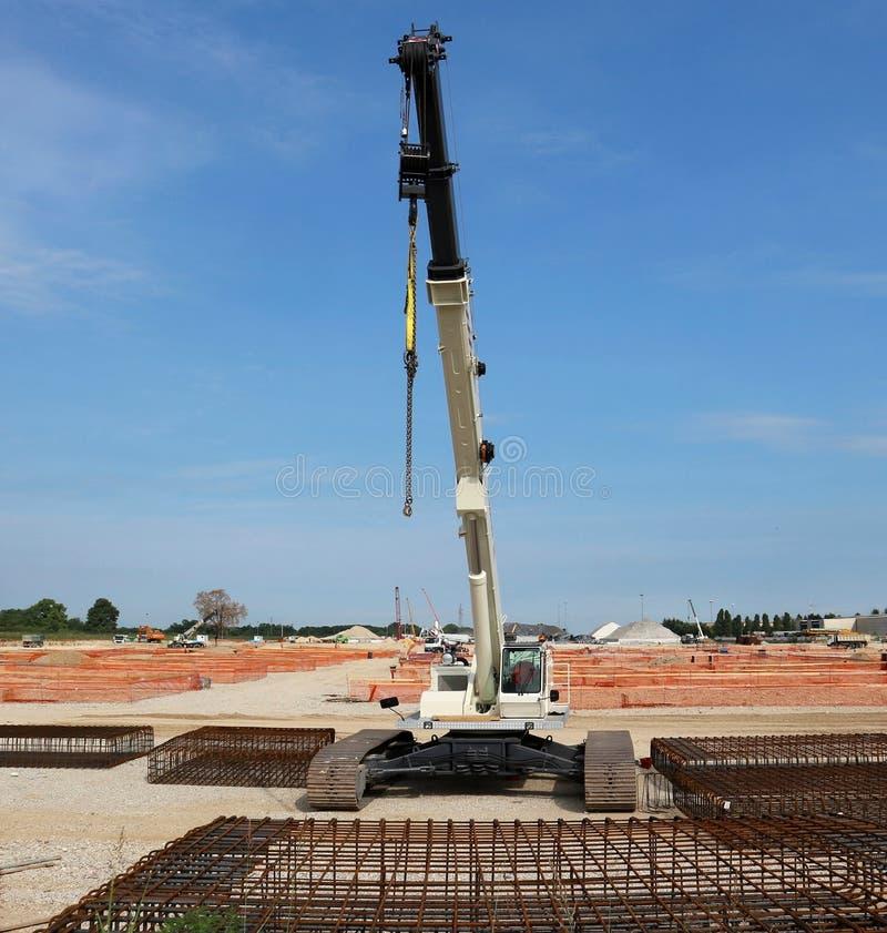 Gevolgde mobiele telescopische kraan in een grote bouwwerf, met staalkooien vooraan royalty-vrije stock afbeelding