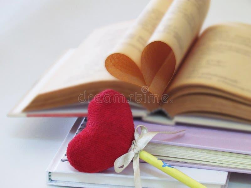 Gevormd die hart van oude boekpagina's en referentie rood hart is wordt het gemaakt iets die moet samen worden gebruikt stock afbeeldingen