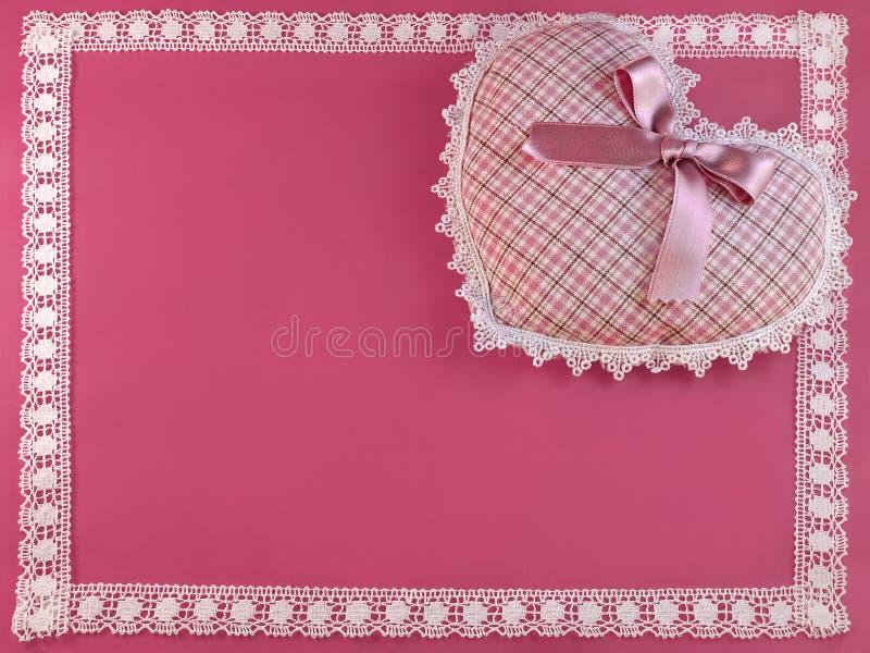 Gevormd hart op roze met een kanten grens stock foto