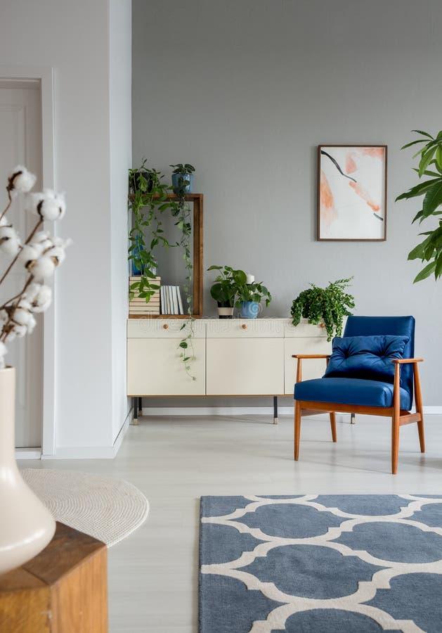 Gevormd tapijt en blauwe leunstoel in grijs woonkamerbinnenland met affiche en installaties Echte foto stock fotografie