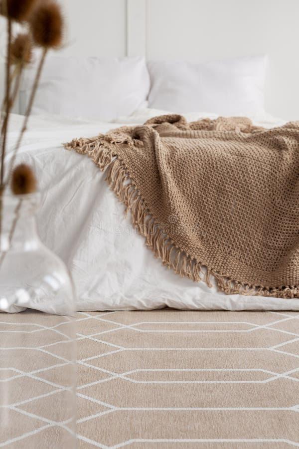 Gevormd tapijt in natuurlijk slaapkamerbinnenland met bruine deken op wit bed stock foto's