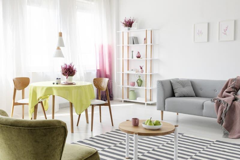 Gevormd tapijt op de vloer van modieuze woonkamer met grijze laag, rondetafel en stoelen en heideschilderijen op de muur royalty-vrije stock fotografie