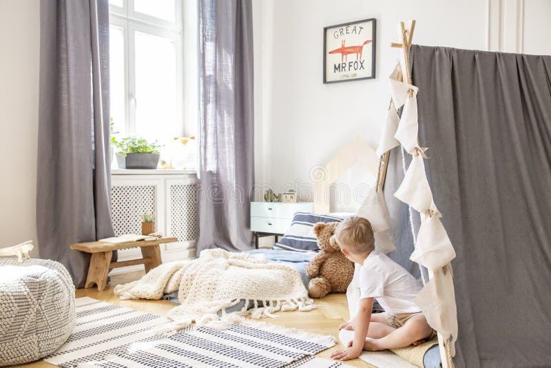 Gevormd tapijt op parket van de slaapkamer van de comfortabele jongen met comfortabel bed en Skandinavische tent, echte foto met  stock foto