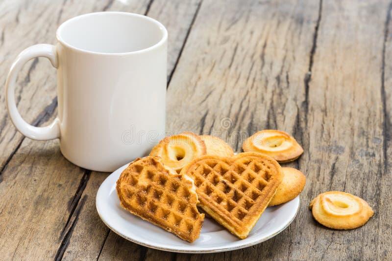 Gevormd wafelshart en koekje op witte plaat en koffiekop royalty-vrije stock foto