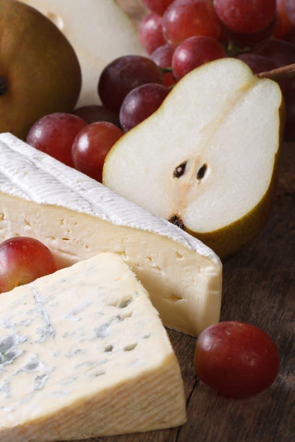 Gevormde kaas, rode druiven en perenverticaal stock afbeeldingen