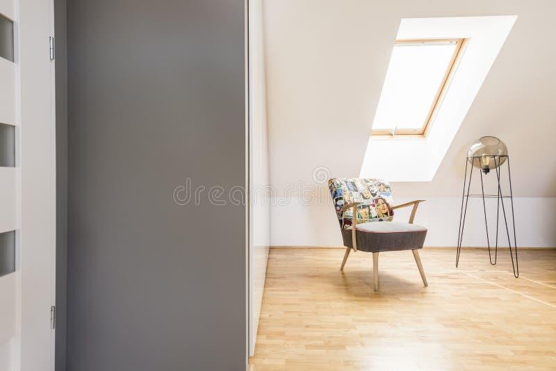 Gevormde leunstoel naast moderne lamp op houten vloer op zolder royalty-vrije stock afbeeldingen
