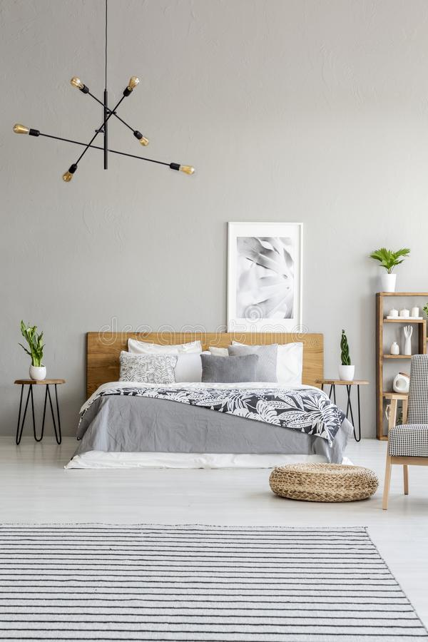 Gevormde tapijt en poef in ruim grijs slaapkamerbinnenland met affiche boven houten bed Echte foto stock foto