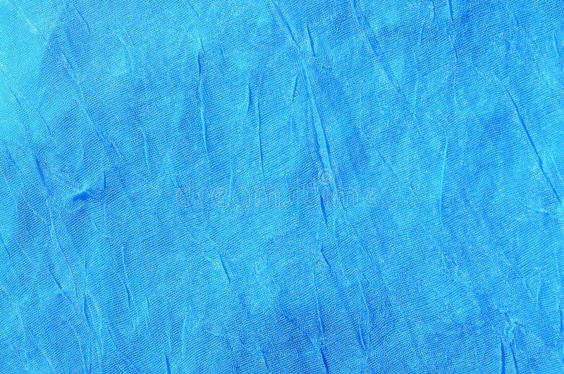 Gevouwen blauw doek materieel fragment als achtergrond textur royalty-vrije stock foto's
