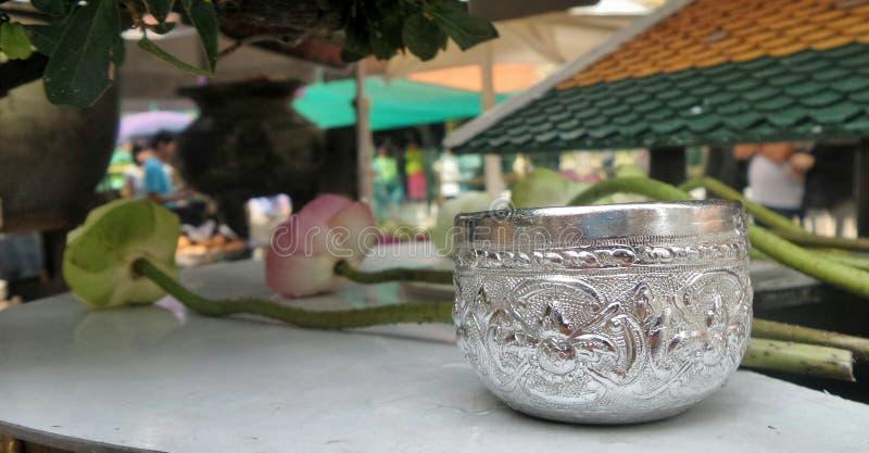 Gevouwen bloemblaadjes heilige lotusbloem en drinkwaterkom voor het betalen van eerbied aan het beeld van Boedha royalty-vrije stock afbeeldingen