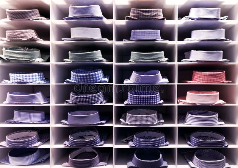 Gevouwen kleurrijke overhemden op klerenrek stock fotografie