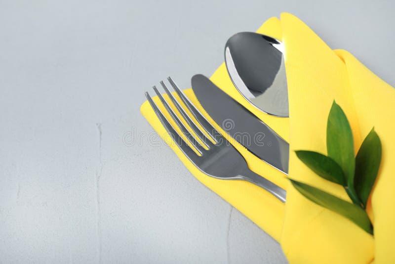 Gevouwen servet met vork, lepel en mes op grijze achtergrond stock afbeelding