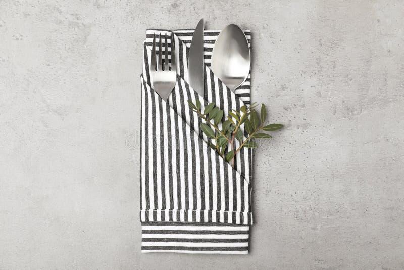 Gevouwen servet met vork, lepel en mes op grijze achtergrond royalty-vrije stock foto
