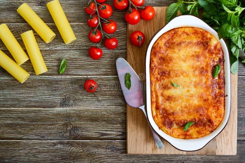Gevulde cannellonien met bechamelsaus Cannelloniendeegwaren met vlees, roomsaus, kaas op een houten achtergrond worden gebakken d stock foto's